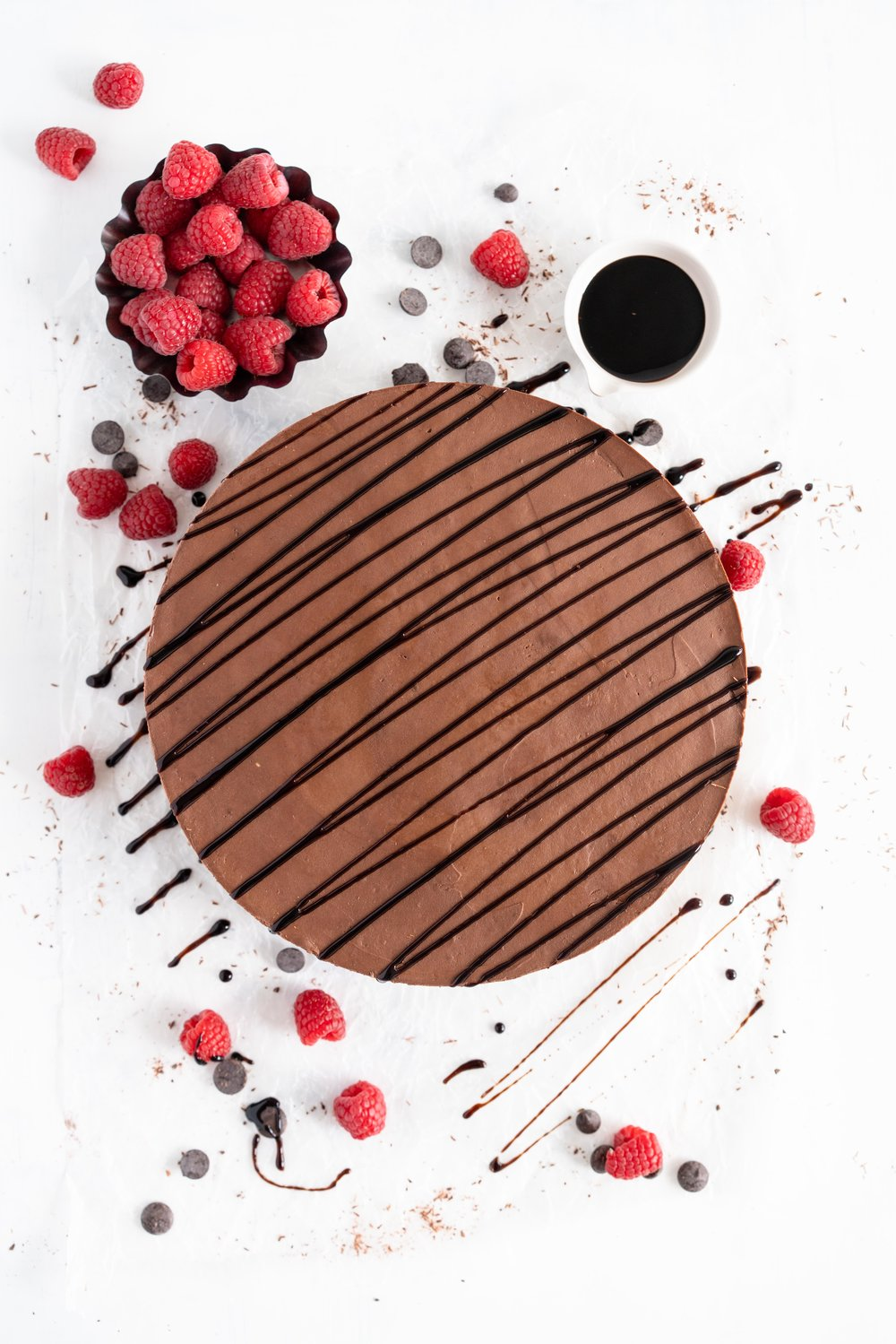 No Bake Chocolate Cheesecake - a chocolate graham cracker base is topped with a silky, no bake chocolate cheesecake filling, and finished with a drizzle of sweet, sticky raspberry balsamic glaze. This dessert comes together quickly, and is perfect for feeding a crowd. #cheesecake #chocolatecheesecake #nobakecheesecake