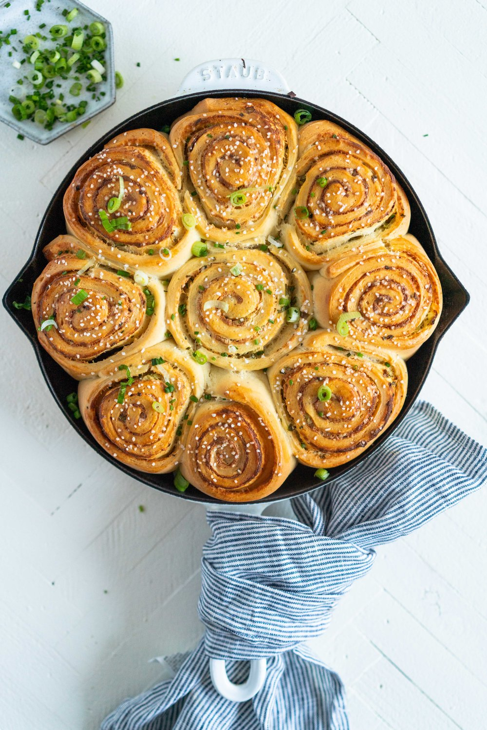 Cheese, Spring Onion, and Chive Brioche Buns - fluffy brioche is rolled out thin, then spread with a cheese sauce filling, sprinkled with spring onion and chives, and rolled up into a tight spiral. It is then cut up into buns, snuggled into a skillet, and baked to golden perfection. The perfect savoury bun! #cheesebuns #cheeserolls #cheeseandchive
