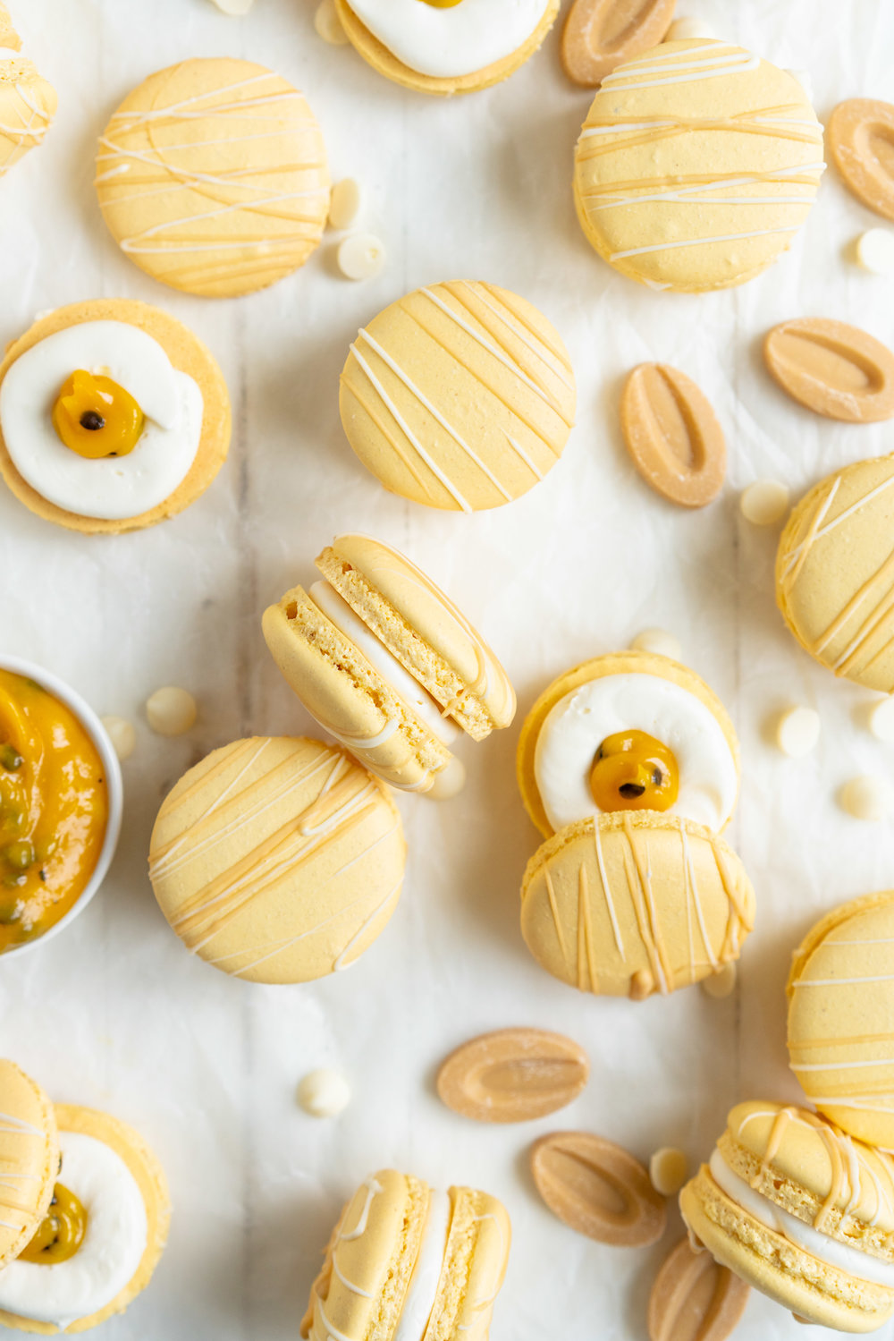 Passionfruit and White Chocolate Macarons - Vanilla bean macaron shell, filled with white chocolate swiss meringue buttercream and tangy passionfruit curd, then finished with a chocolate drizzle. #frenchmacaron #macarons #passionfruit