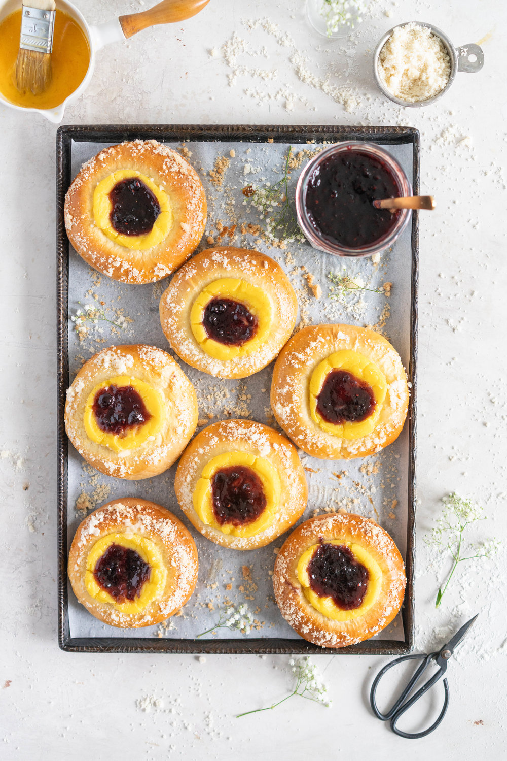 Custard Brioche Buns with Bonne Maman Mixed Berry Preserves and Vanilla bean Streusel. Light and fluffy brioche rounds are filled with a vanilla bean custard, then finished with a swirl of Bonne Maman Mixed berry preserves, and a sprinkle of vanilla bean streusel. These are perfect for a super easy but incredibly delicious brunch, as everything can be prepared the night before, making assembling the next morning super easy. #brioche #custardbun #breakfastpastry