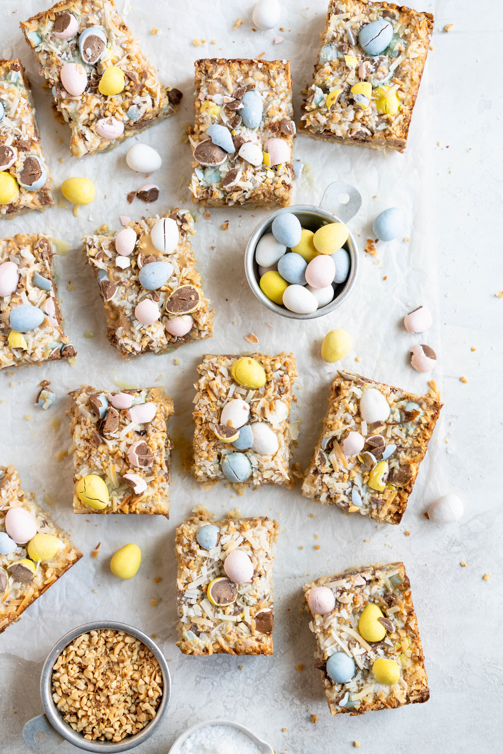 Mini egg magic bars are the ultimate Easter baking treat - a toasted hazelnut shortbread base is topped with a condensed milk topping, filled with mini eggs, shredded coconut, chopped hazelnuts, and caramelised white chocolate. These are super easy to make, and amazing for using up any leftover Easter candy you may have! #magicbars #minieggs #7layerbars
