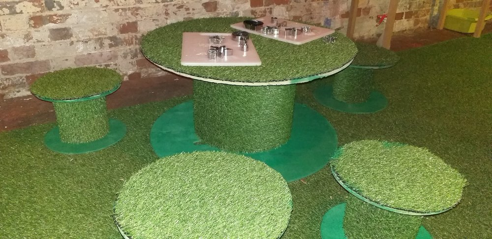 A grass covered table for children to sit at to make their flowers