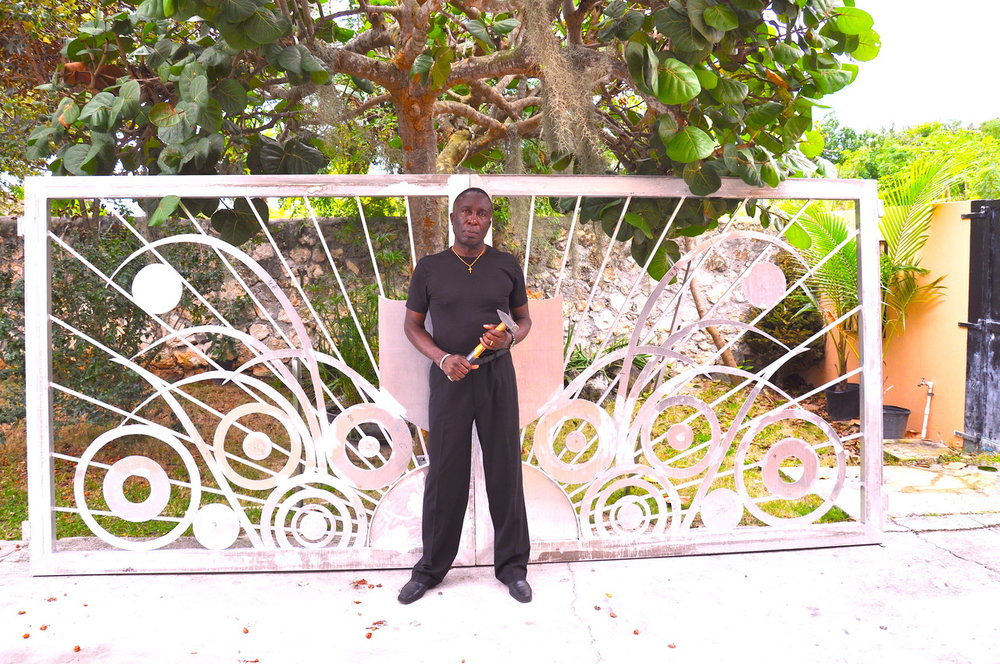 Portrait of Tyrone Ferguson in front of privately commissioned gates. Image courtesy the artist.