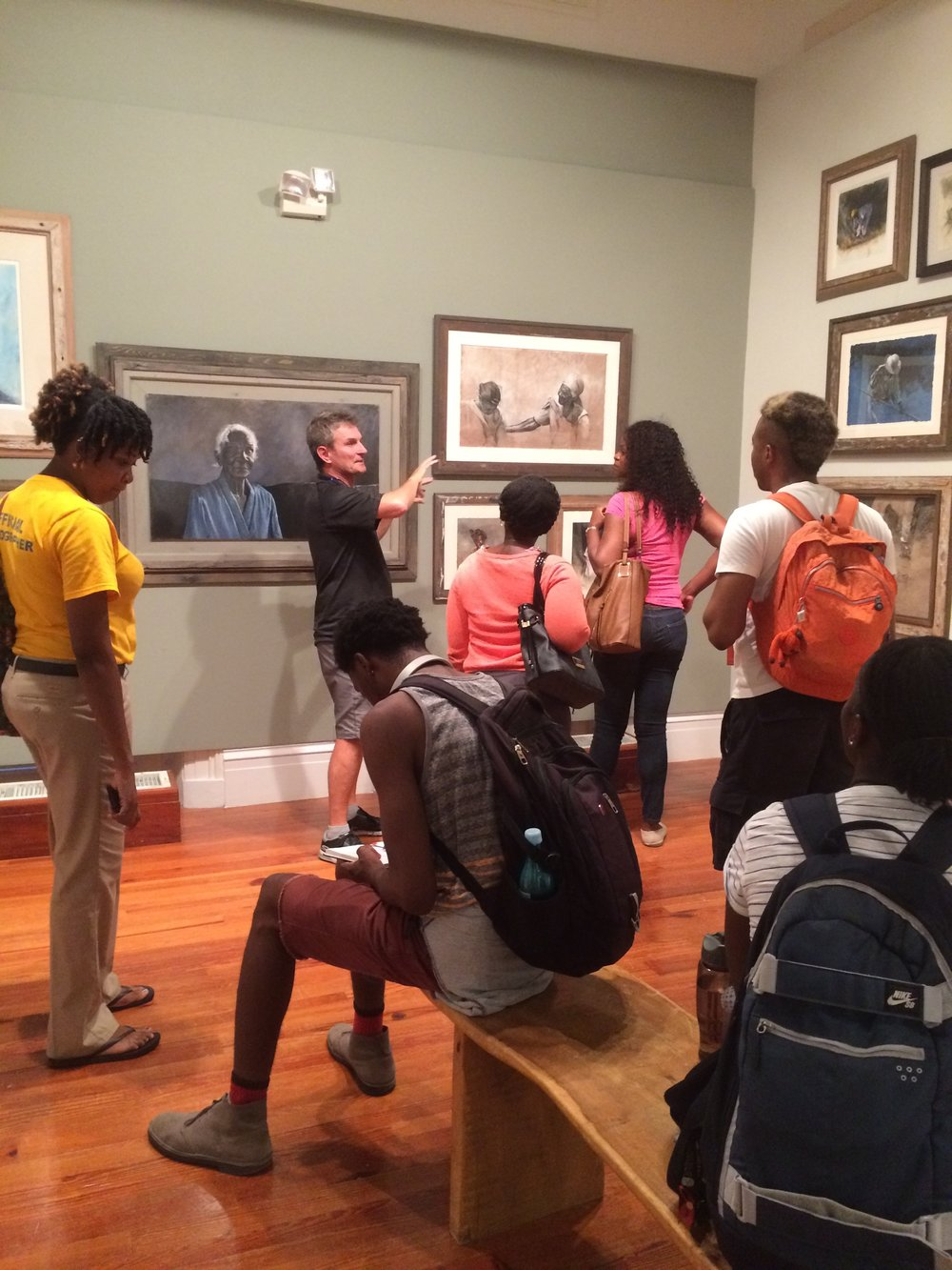 "University of The Bahamas students visit Thierry Lamare's ""Love, Loss and Life"" on view at the National Art Gallery of The Bahamas and receive a guided tour by the artist. Images courtesy of Dr. Ian Bethell-Bennett."