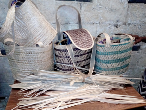 A display of various straw bags and silver top straw palm leaves