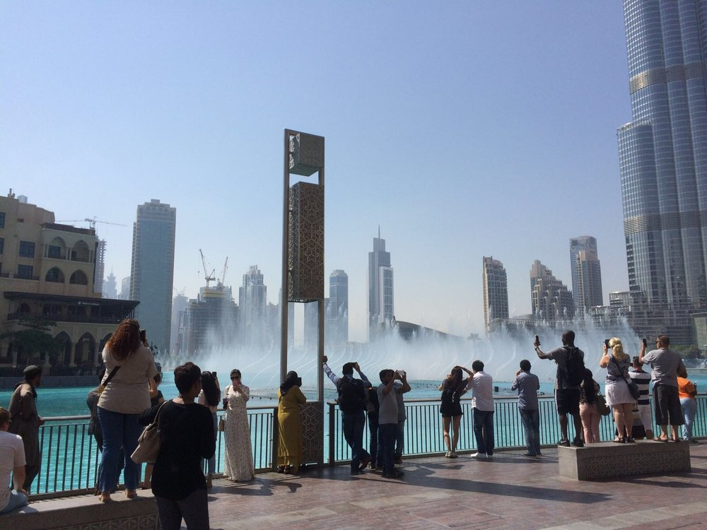 Skyline of Dubai with water works and tourists.
