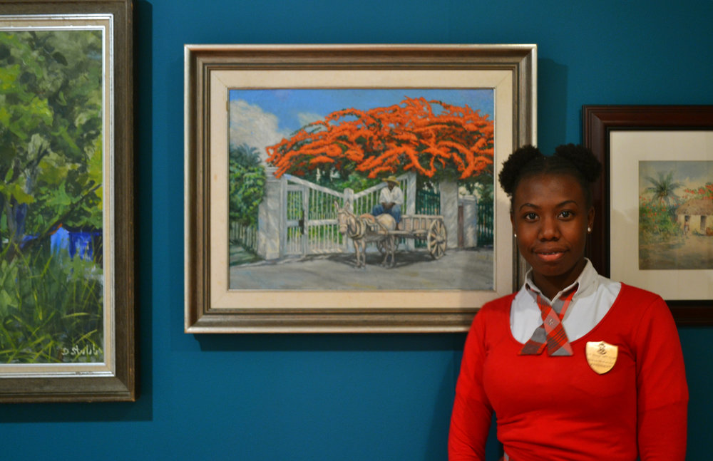 "Nakoa McKenzie stands with Sweeting's painting ""Two Natives at the Gate"" showcased in the permanent exhibition, ""Revisiting an Eye For The Tropics"" on view at The National Art Gallery of The Bahamas through the end of March 2018. Images courtesy of The NAGB."