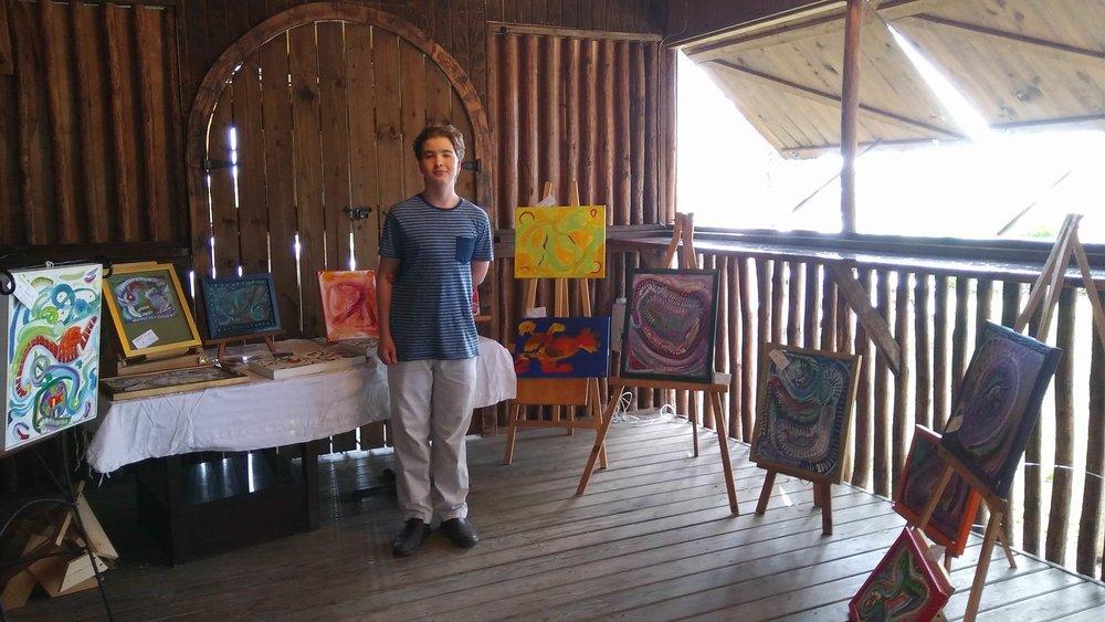 Lucas Kaighin with his paintings.jpg