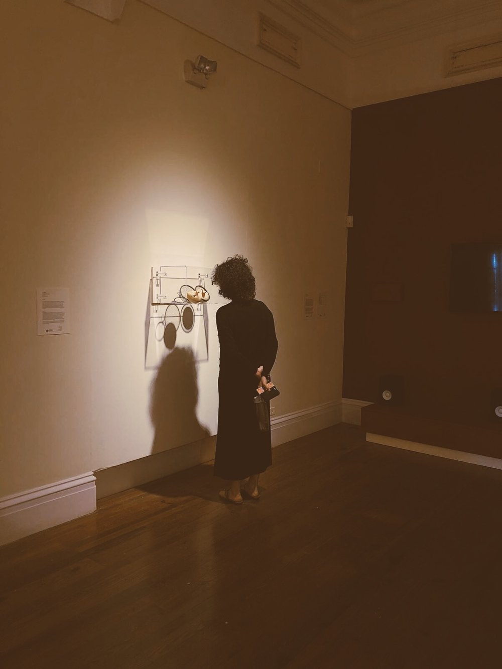 "Holly takes in a piece created by Bahamian artist Anina Major from the exhibition ""We Suffer to Remain."""