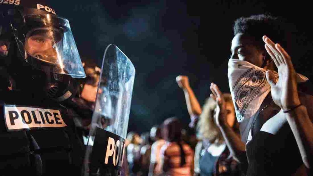 CHARLOTTE, NC: Protesters and police face off after the shooting of a black man by a black police officer. Image courtesy NPR News.