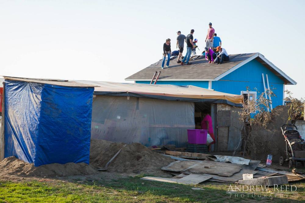 In the front you can see the temporary structure the family lived in - dirt floor, tarps for walls and no insulation.