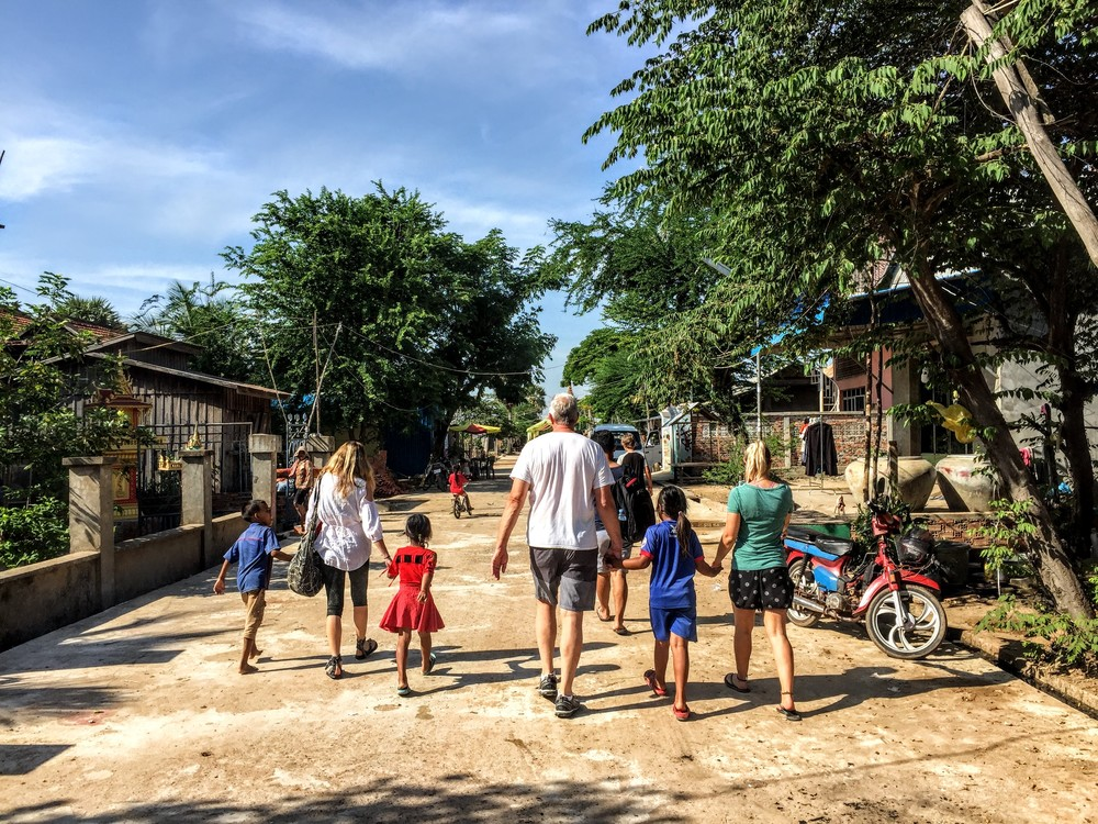 Natalie, Mike and Me walking through the village naturally gathering more and more children along the way