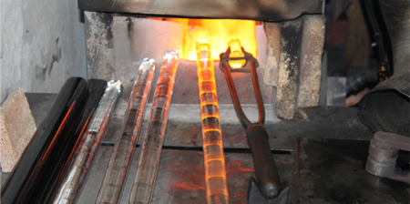 Dozens of glass rod colors - standardized by a numbering system used in all shops -- have the potential for being highlighted or combined with other colors in a single button. In the forge above , several rods are heated in phases to assure production will move quickly when the presser begins.