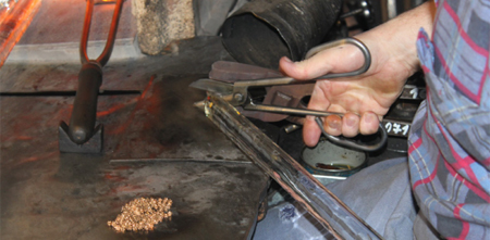 The presser shears the molten glass from the rod and then opens the mold to reveal the formed button.