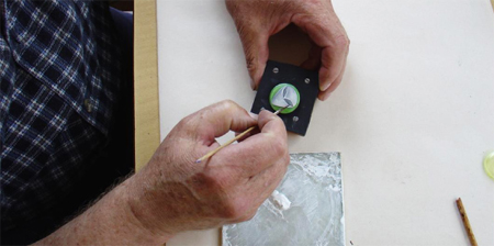 Practiced artisans finish each button detail by hand with leafing and other traditional, durable paints.