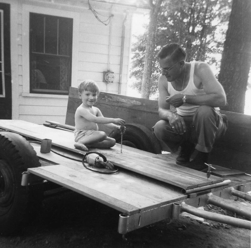 Norm as a youngster working with his dad on their trailer