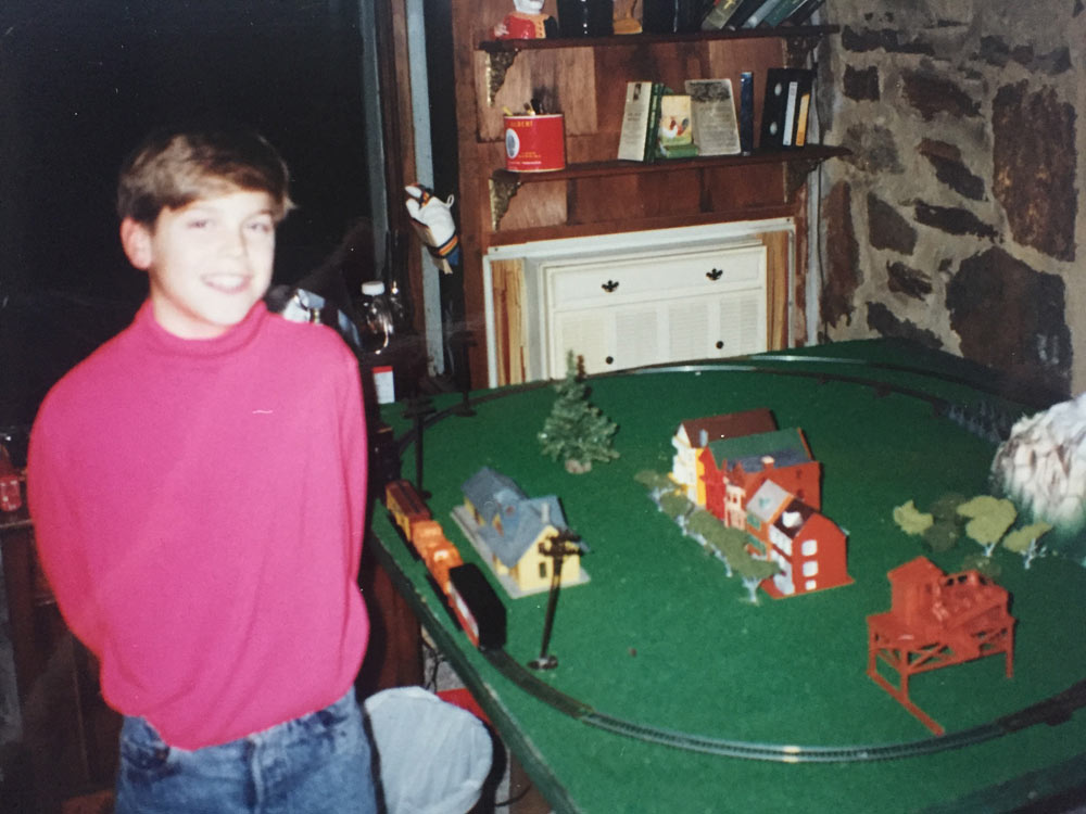 "Drew posing in front of ""my first urban planning attempt, a very depressing train set with models of the Pink Ladies of San Francisco."" Baltimore, 1990"