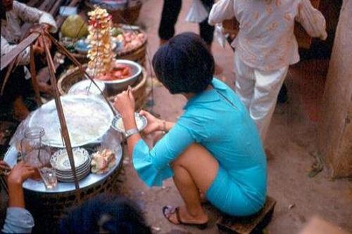 Một quý cô ăn hàng trên vỉa hè trong bộ đầm ống tay loe sành điệu.