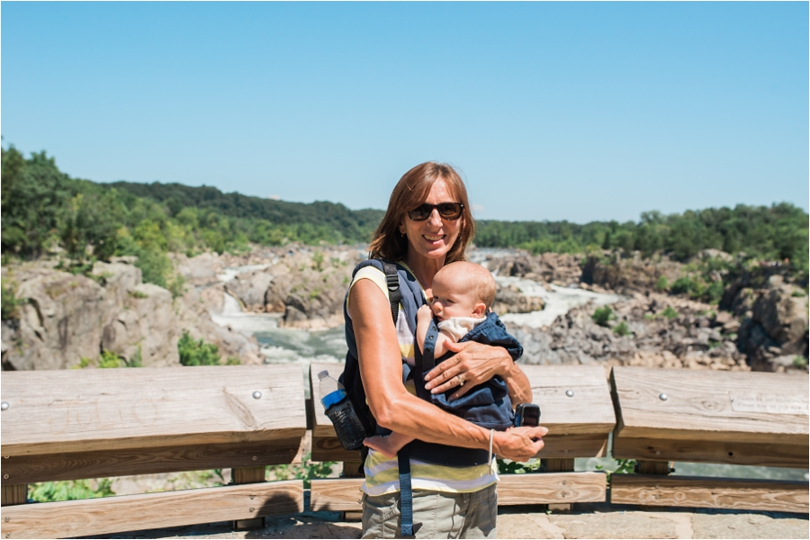 Allie's Mother wearing on of the twins on the front and a backpack on the back at Great Falls.