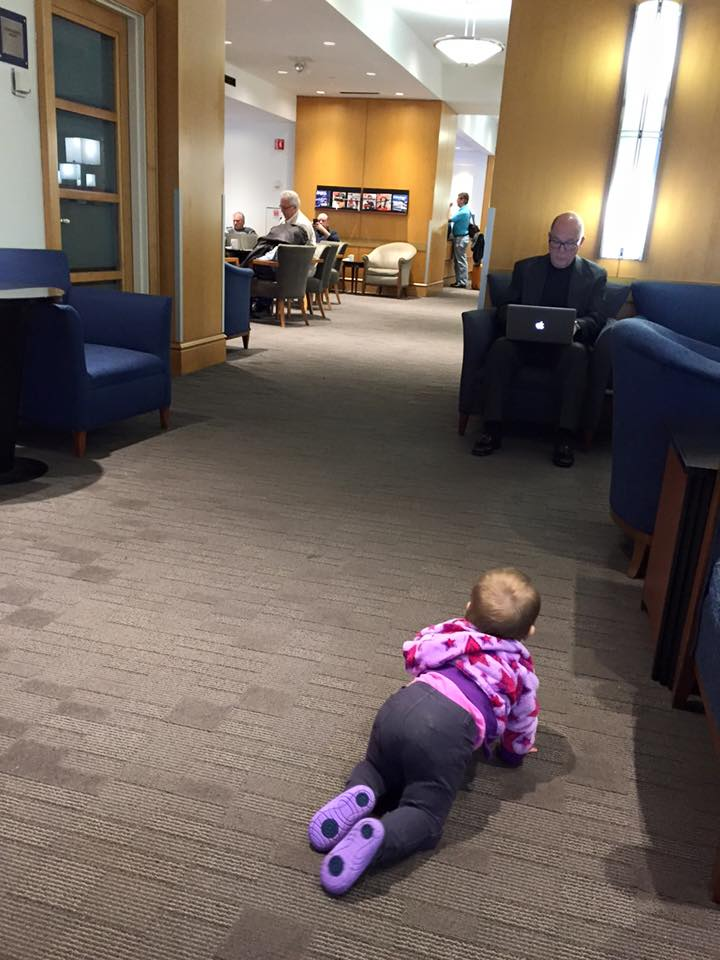 My daughter crawling around the Delta Sky Lounge while a business man is working