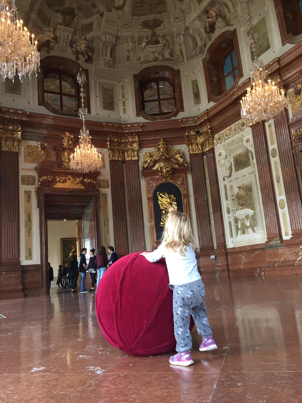 Her pushing around the giant balls in marble hall
