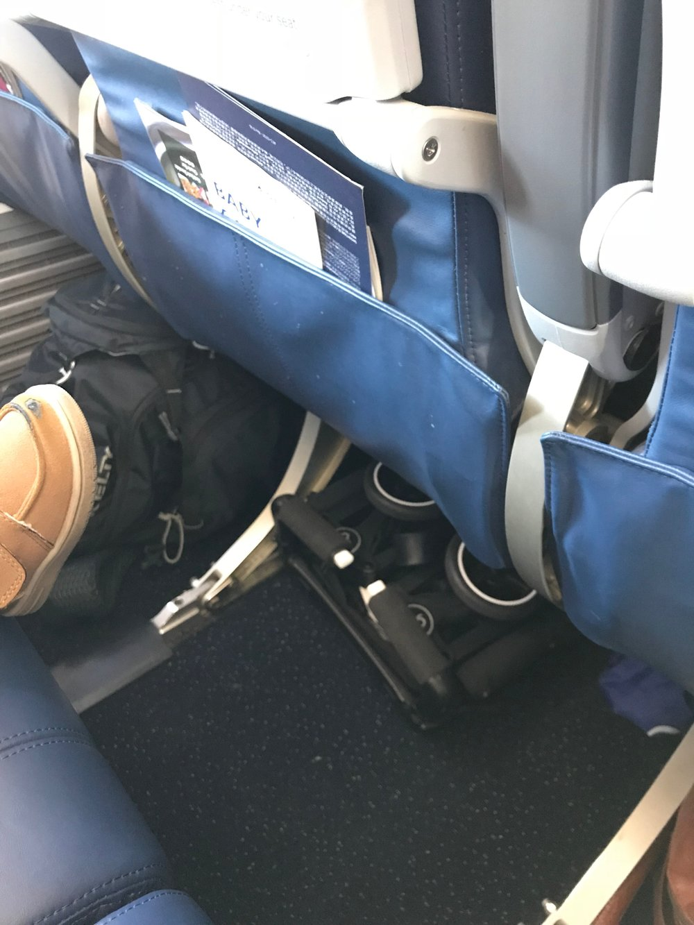 Our tiny GB Pockit Stroller underneath the airplane seat