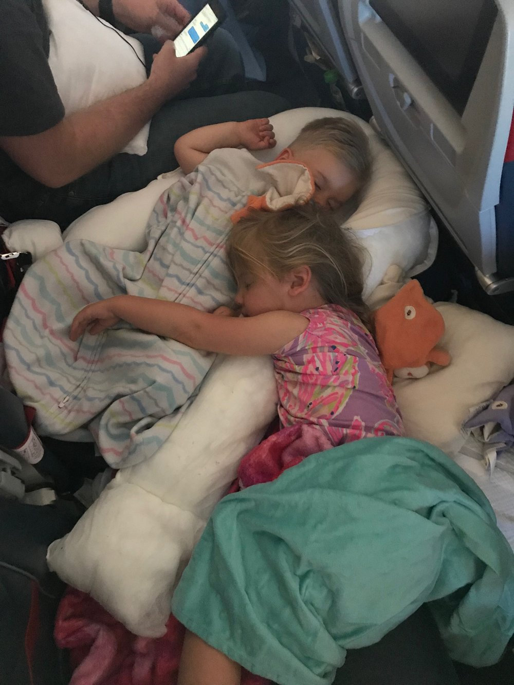 using the inflatable foot pillows to extend the seat so the kids could lay down on a long haul from atlanta to amsterdam-- you can still use a seatbelt in this configuration (see photo from tip 3)
