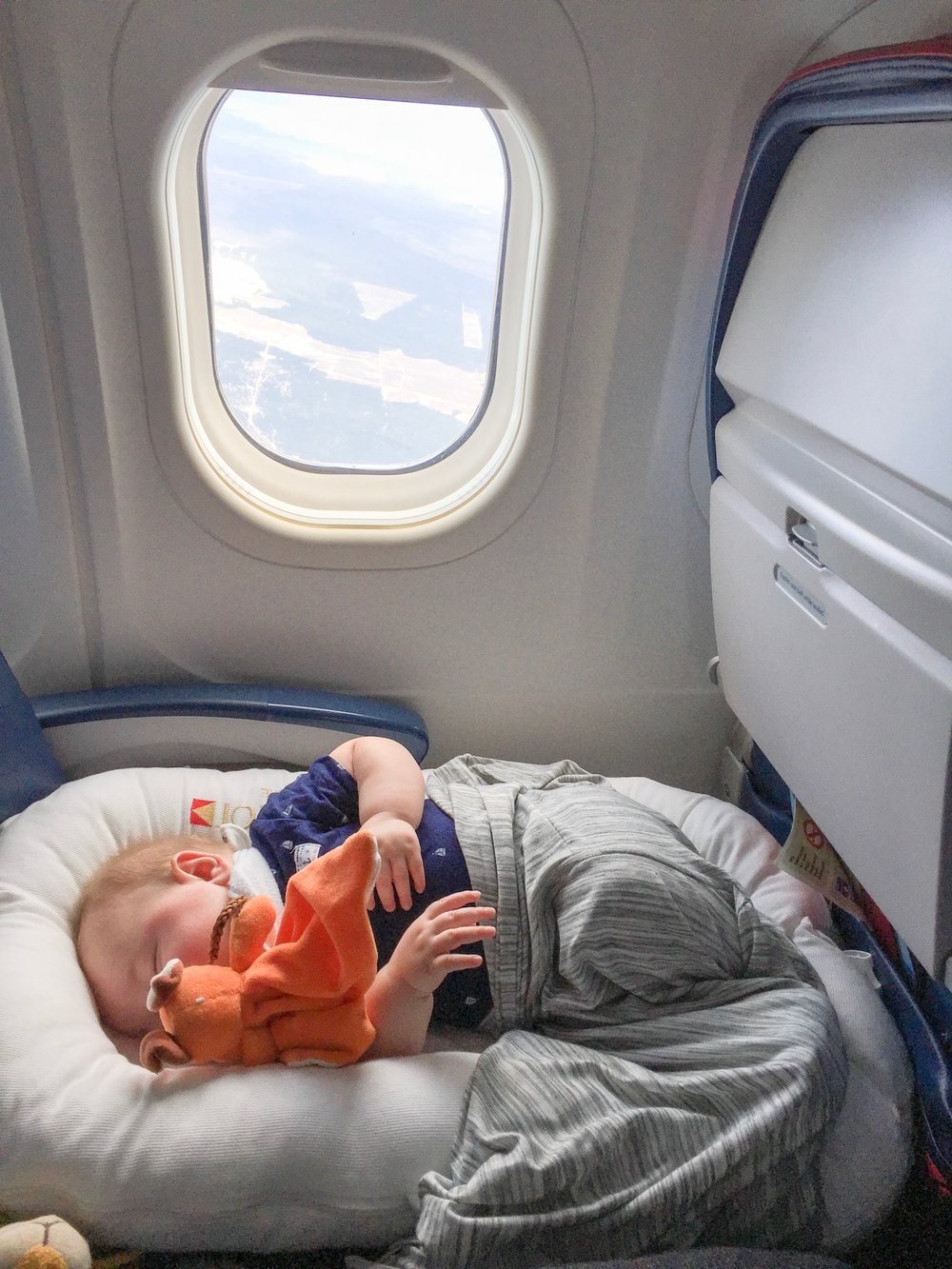 Latham using his DockATot DeluXE here and snoozing away a flight from Amsterdam to Prague.
