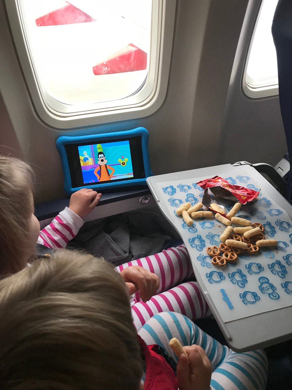 The kids eating snacks on a domestic flight; they are using their oogaa silicone mat to keep the snacks germ free.