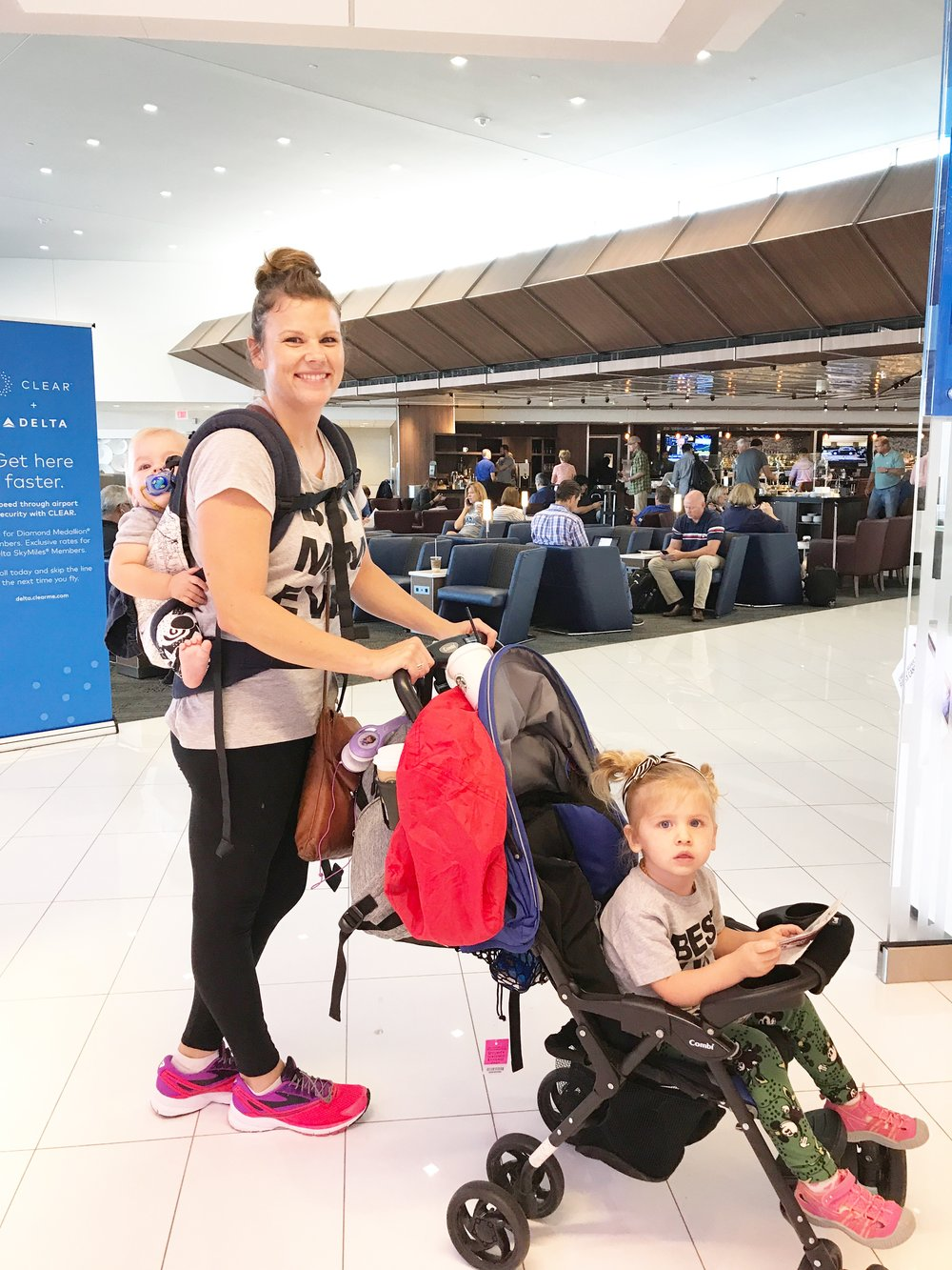 While this isn't me actively lulling a baby to sleep ON a plane, it is me getting 2 kids through the airport by myself. I highly recommend investing in a baby carrier
