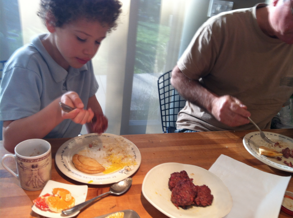 Older brother Anthony set the tone for eating with enjoyment. Breakfast with grandpa; home-made sausages in the foreground.   Chinatown plates by Steve Wong.