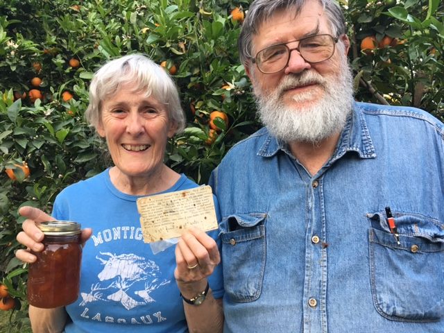 Elizabeth and Paul Barber holding Rangpur lime marmalade and her mother's recipe card. The massive tree filled with these fruits is behind them.