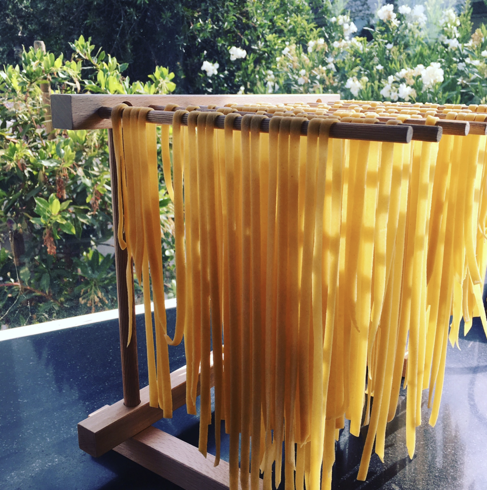 Light glowing through fettuccine on the drying rack.