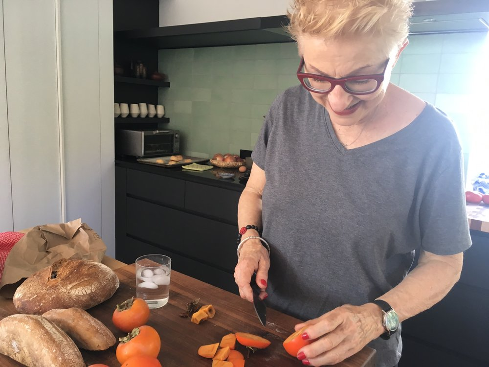 "Anna Thomas beginning her Fuyu Persimmon Salsa in my kitchen. (The persimmons were ""foraged"" from her neighbor's tree.)"