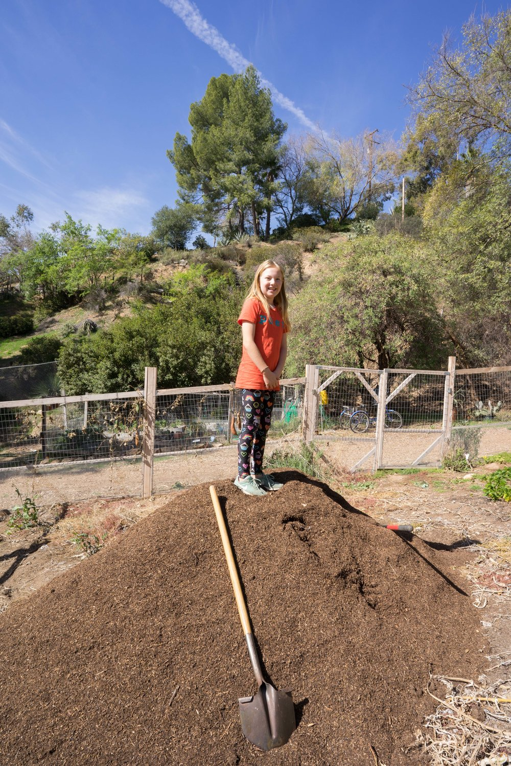 Charlotte McDonald standing on the compost pile. She is planting her own micro-garden of edible flowers and herbs and is a budding entomologist.