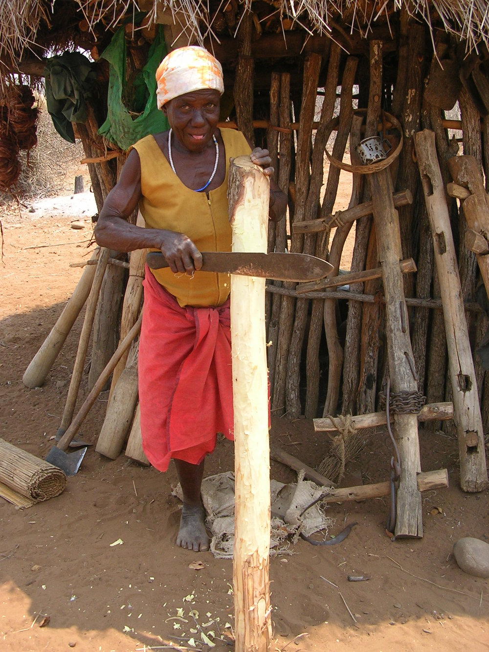 Meselina is preparing the tools she needs for food preparation to bring them to the new location. She is afraid that she will not find the wood that she needs there to make them. (2008)