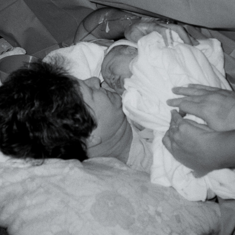 This gorgeous birth photo shows mother sharing a sweet moment with her newborn baby after a c-section procedure.