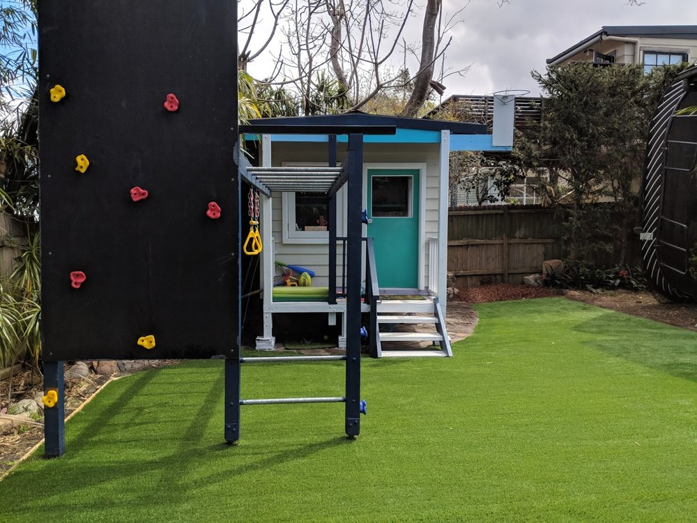 This area didn't grow grass very well and was either dusty or muddy. Premium synthetic grass was used to give a great space for the children to play in.