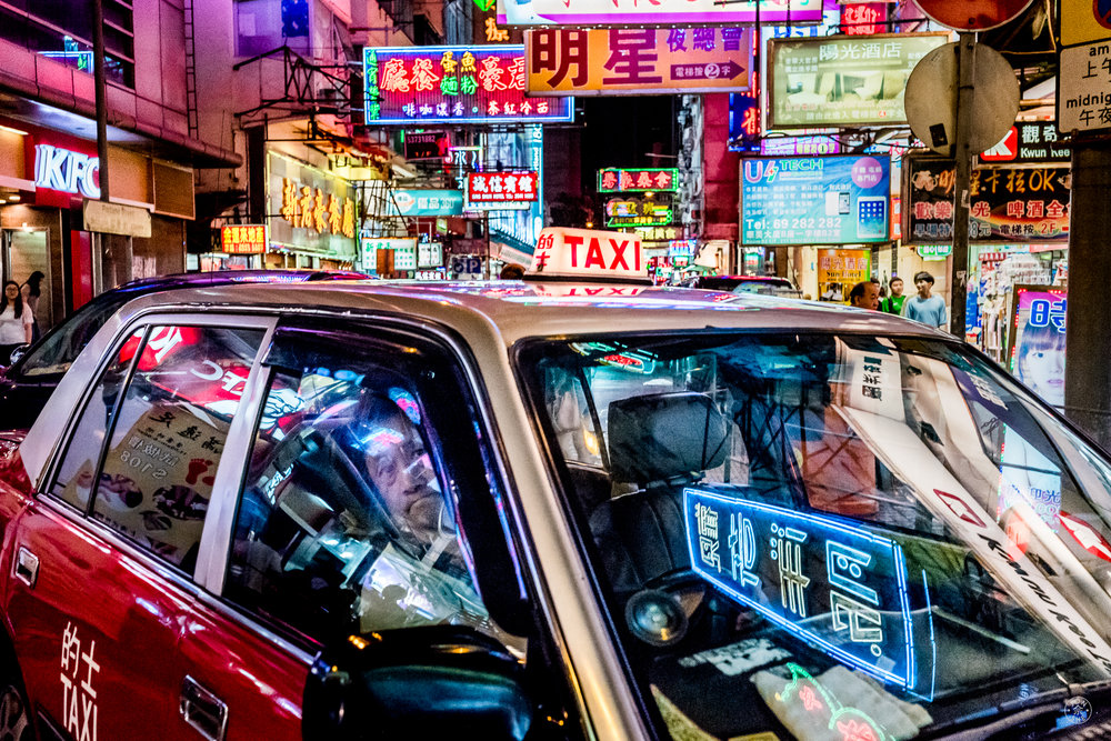 """Neon Taxi"".  These red-and-white cabs are ubiquitous on the congested streets of the city, and along with the trams an iconic element of the supercity. I tried to capture as many iconic HK elements as I could in this one picture by getting up close to the vehicles in the foreground, and having the neon signages in the background and also on the windshield. Leica SL (Typ 601), Leica Summilux-M 35mm f/1.4 Aspherical. Kowloon, Hong Kong, China. July 2016. © Jon She."