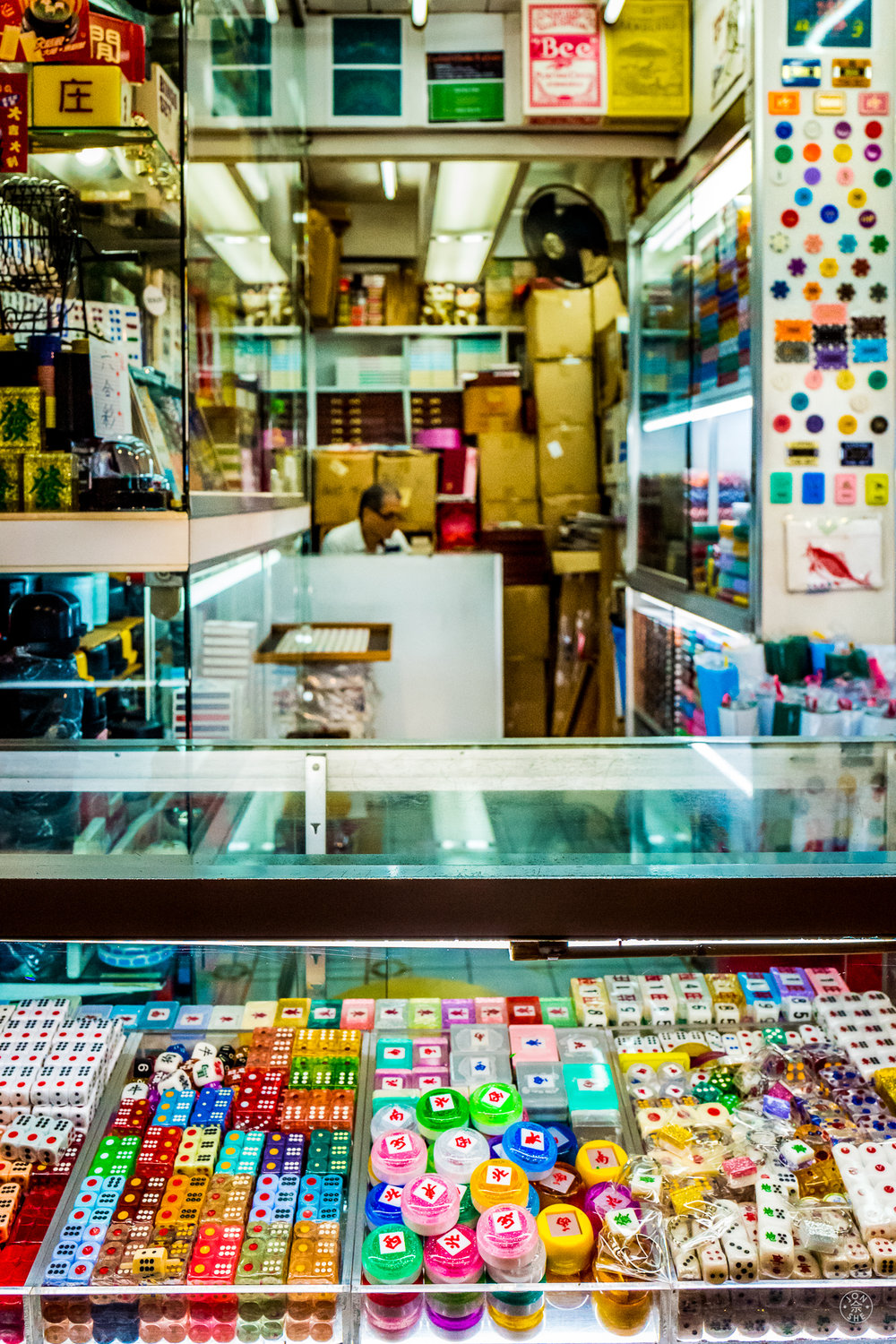 """Gambling and Gaming Supply Store"". Late night gaming and gambling dens are another common site in Hong Kong, as are vendors that support that nocturnal ecosystem.  This shot is of a supplier of dice, chips, mahjong tiles, cards, and the myriad other paraphernalia needed for games.  Kowloon, Hong Kong, China. June 2016. Leica Q (Typ 116), Leica Summilux-M 28mm ASPH. © Jon She."