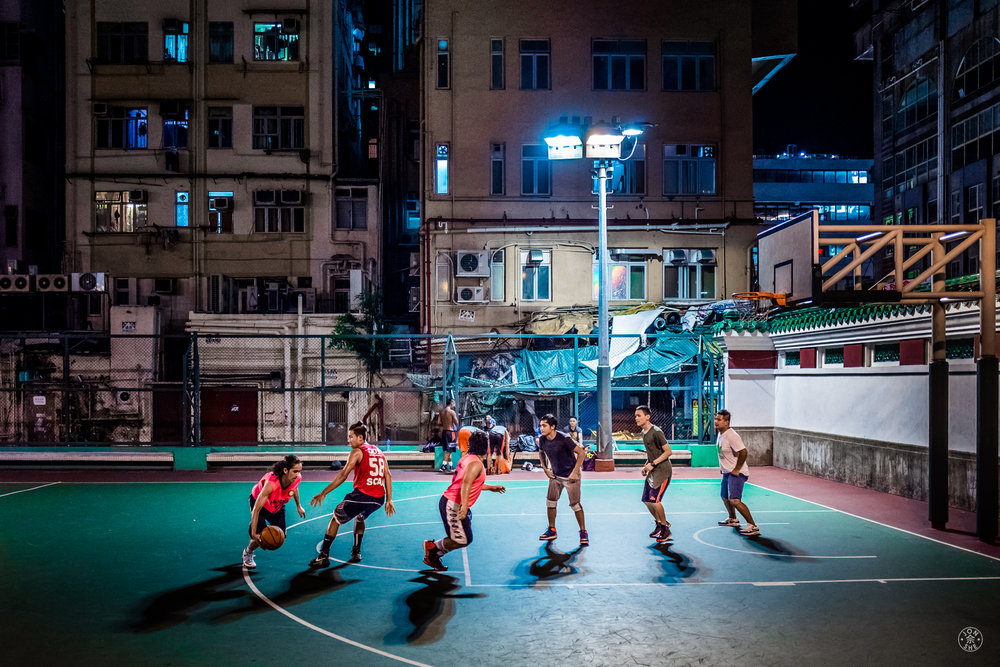 """Late Game"". I came upon this group of young men playing basketball on a court in the middle of a cluster of old apartment buildings, late in the evening.  I tried to have a decent depth of field in order to get details of the buildings in the backdrop, while still having an aperture wide enough for a shutter speed to capture the moving players. Kowloon, Hong Kong, China. June 2016. Leica Q (Typ 116), Leica Summilux-M 28mm ASPH. © Jon She."