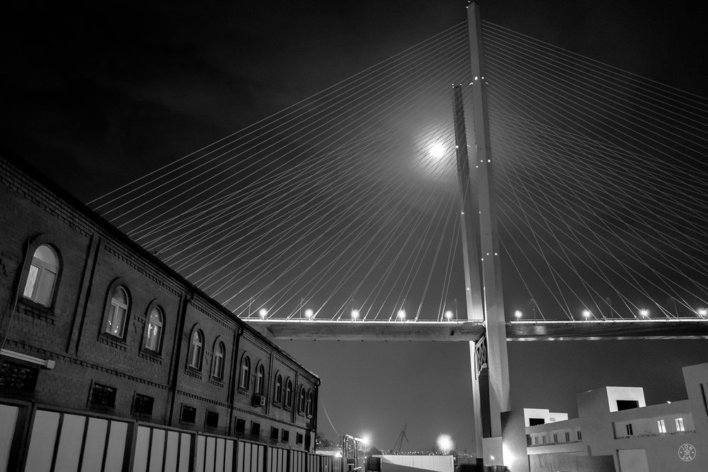 """Zolotoy Bridge at Night"".   Like a geometric Colossus the ""Golden Horn"" bridge dominates the winter skyline from almost everywhere in the city, linking the old to the new.  Vladivostok, Primorsky Krai, Far East Russia. January 2017. © Jon She. Leica Q (Typ 116), Leica Summilux 28mm f/1.7 ASPH (FLE)."