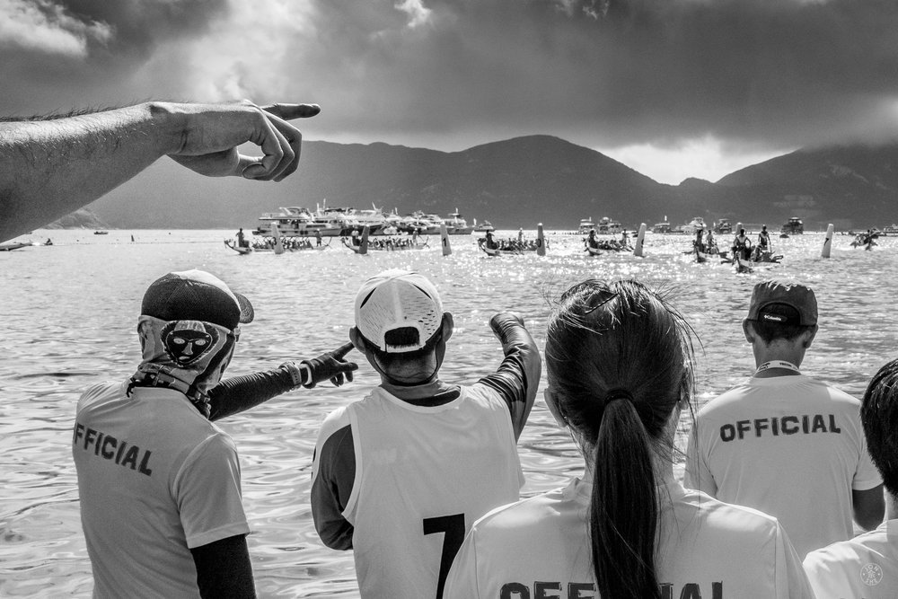"""Thunderstorm on the Horizon"".  Dragonboat Festival Race participants preparing for rain on Stanley Beach. Hong Kong, China. June, 2016. © Jon She. Leica Q (Typ 116), Leica Summilux-M 28mm ASPH."