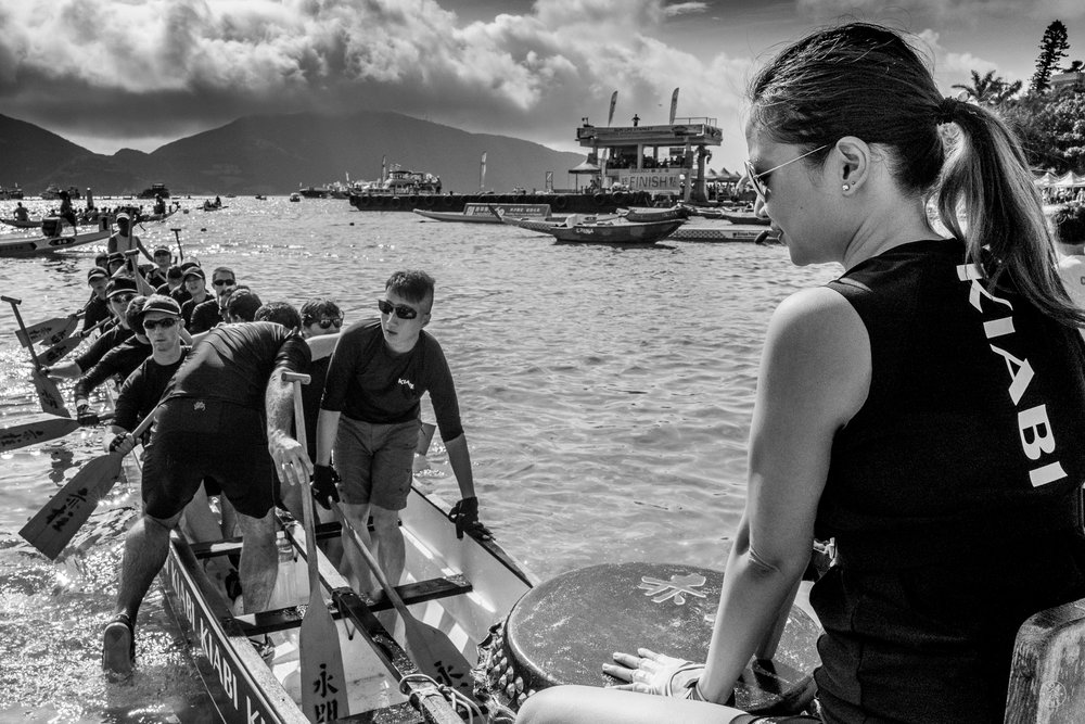 """Racing into the Storm"".  A Dragonboat Festival Race team prepares to challenge a rainstorm rushing onto Stanley Beach. Hong Kong, China. June, 2016. © Jon She. Leica Q (Typ 116), Leica Summilux-M 28mm ASPH."