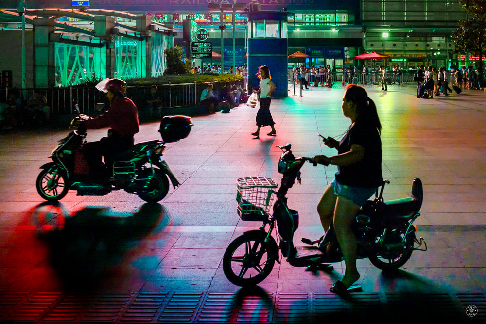 """Do Motorbikes Dream of Color Shadows?"".  A view from the plaza in front of a railway station.  There was a football field-sized LED screen on the facade of the station playing advertisements that cast interesting colors and shadows of passerby and traffic on the plaza. Shanghai, China. August 2016. © Jon She.Leica M-P (Typ 240), Leica Summilux-M 35mm f/1.4 ASPH (FLE)."