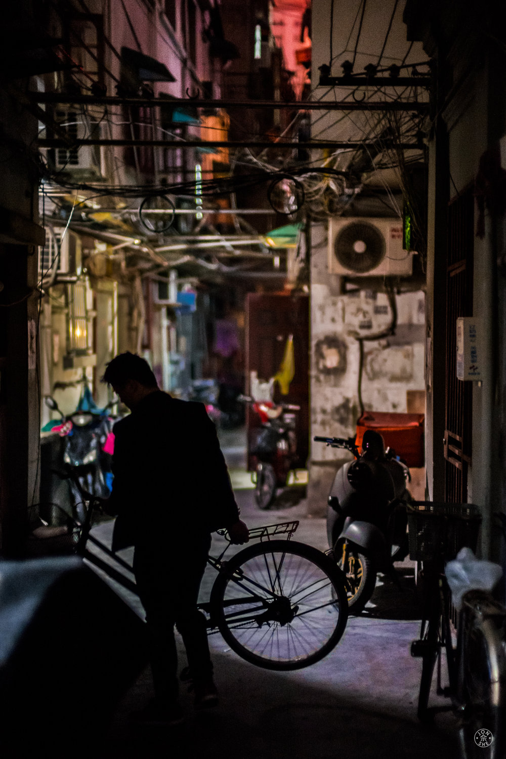 """Arriving Home"".  A young man gets back home late at night on his bicycle, in a back alley in Shanghai. Hundreds of thousands of the city's residents still live in congested and relatively undeveloped back alley communities like this one, often just around the corner from a modern road or skyscraper. Shanghai, China. May, 2016. © Jon She. Leica SL (Typ 601), Leica Noctilux-M 50mm ASPH."