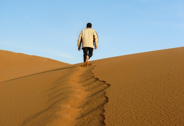 A man walks uphill in the desert sand