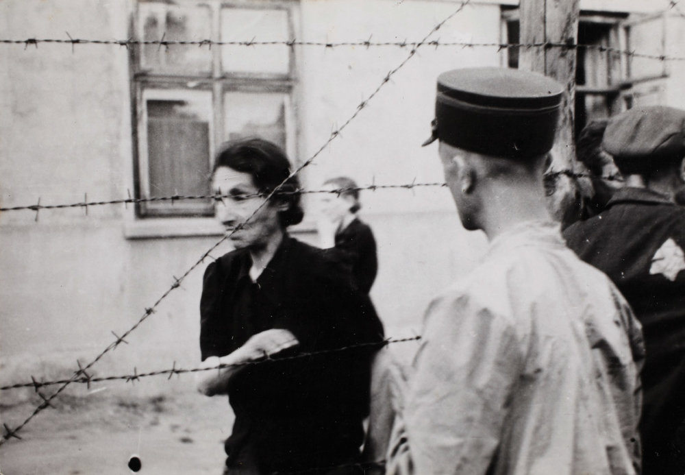 Henryk-Ross-Ghetto-police-with-woman-behind-barbed-wire.jpg