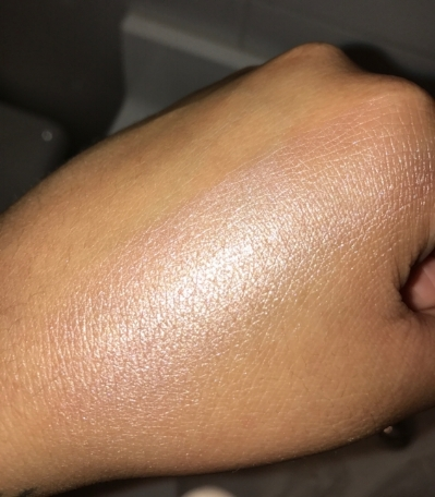 "This is a swatch on my medium skin tone (with flash) & The beam is real!!! It will photograph beautifully. This is in the shade ""Champagne""."