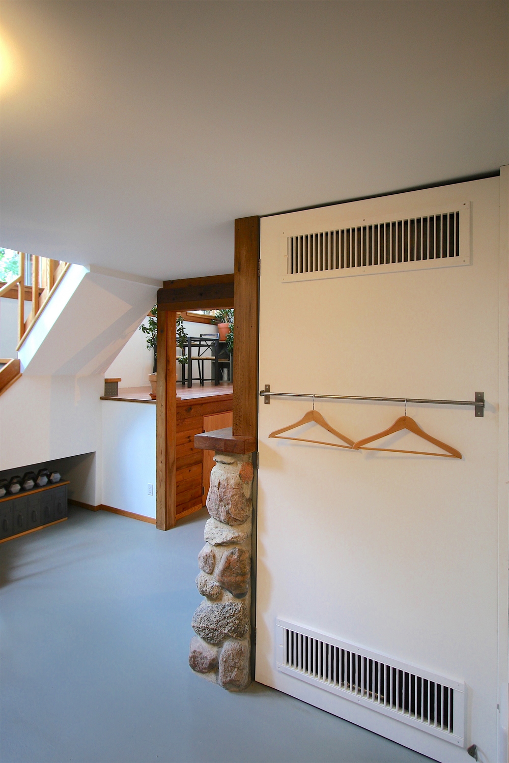"A unique energy-saving feature is this heat-circulating ""radiant wall"" at the back of the fireplace. Simply give your clothes a shake when you take them out of the dryer and hang them here for ""free"" drying...  (This steel-studded concrete-boarded wall hinges outward to allow periodic access to the back of the airtight woodstove and for chimney cleaning)."